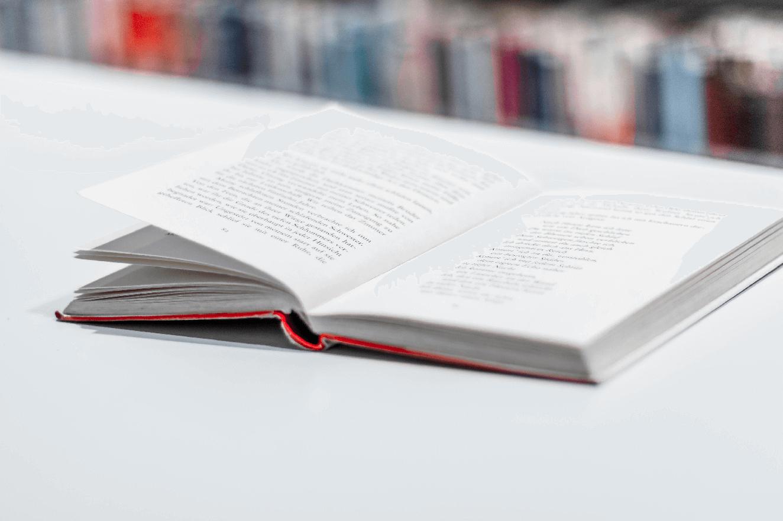 Aufgeschlagenes Buch liegt auf einem Tisch in Bibliothek